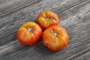 três tomates em uma placa de madeira foto