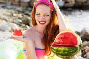 menina sorridente com sardas segurando melancia foto