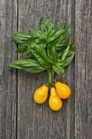 tomate amarelo com manjericão na placa de madeira foto