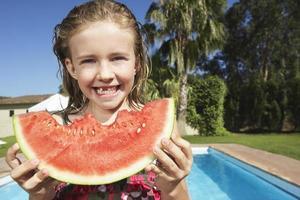 garota comendo melancia contra piscina foto
