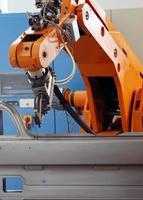 um braço de robô eletrônico laranja em uma linha de montagem
