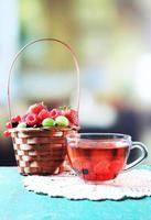 bagas da floresta na cesta e xícara com chá de frutas foto