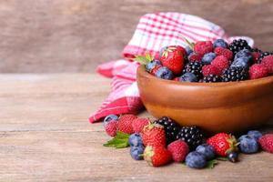 frutos maduros doces diferentes na tigela, na mesa de madeira velha foto
