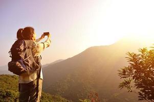 alpinista de mulher tirando foto com telefone celular