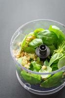 ingredientes para o molho pesto no processador de alimentos foto