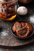 tomates secos ao sol no prato de cerâmico na placa de madeira foto