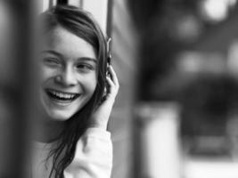 menina sorridente, falando no celular foto