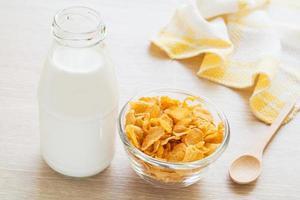 tigela de cereal e garrafa de leite na mesa foto