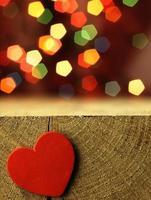 coração vermelho à beira de uma mesa de madeira.