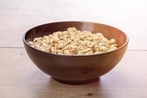tigela preta de cereais em uma mesa de madeira foto