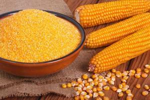 grumos de milho na tigela, grãos e espiga na mesa de madeira.
