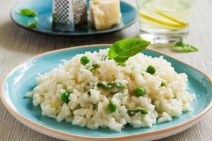 uma porção de risoto com aspargos e ervilhas em um prato azul foto