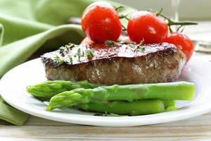 bife de carne grelhada com guarnição de legumes (aspargos e tomates)
