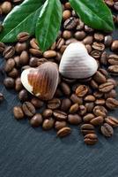 grãos de café e bombons de chocolate em forma de coração foto