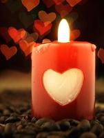 vela vermelha e café na mesa. corações em segundo plano.
