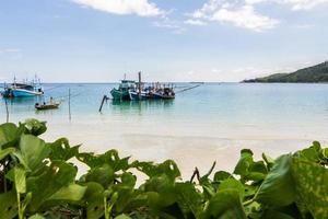 barco de cauda longa e a praia e o céu azul foto
