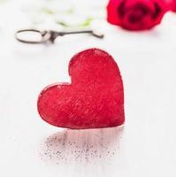 grande coração de madeira vermelho sobre rosa e chave, dia dos namorados foto