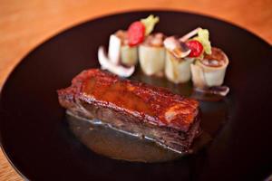 carne de filé e rolinhos primavera com vários legumes foto