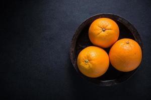 fazenda frutas frescas de laranja em tigela rústica foto