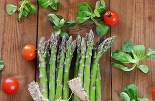 espargos orgânicos na mesa de madeira foto