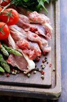carne crua, costeletas de cordeiro com legumes na placa de madeira foto