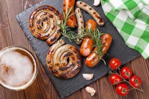 caneca de cerveja e salsichas grelhadas foto