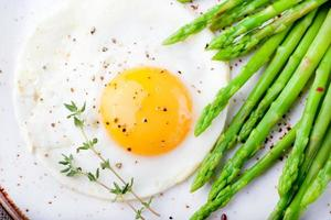 aspargos verdes, ovo frito e pão com manteiga. foto