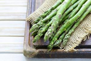 espargos orgânicos verdes frescos em um fundo de madeira foto