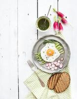 conjunto de café da manhã saudável. ovo frito com aspargos, rabanetes, molho verde foto