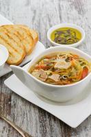 sopa de galinha rústica com macarrão e sobre fundo de madeira foto