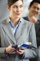 empresária no terminal do aeroporto, segurando o telefone e o bilhete foto