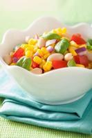 salada de milho saudável com tomate cebola manjericão feijão branco foto