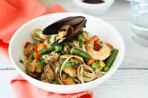 macarrão com legumes e frutos do mar em uma tigela foto