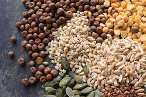 sementes de grãos de arroz e leguminosas no fundo da ardósia foto