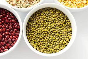 conjunto de diferentes grãos e trigo sarraceno em tigelas brancas foto