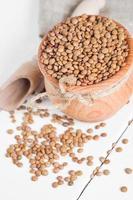 lentilhas marrons orgânicas secas contra um fundo de madeira foto
