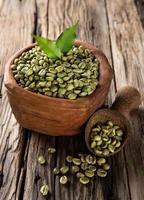 grãos de café verdes em uma tigela de madeira foto
