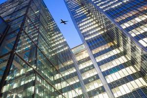 silhueta de avião a jato com escritório comercial edifício fundo de torres foto