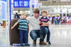 pai e dois meninos irmãos no aeroporto