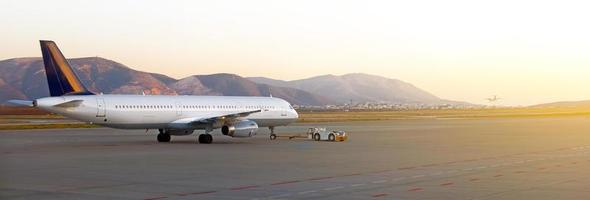 rebocador pushback trator com aeronaves na pista no aeroporto. foto
