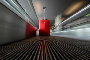 escada rolante em movimento borrado com carrinho vermelho no aeroporto foto