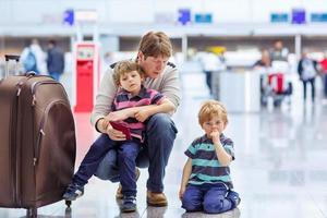 pai e dois meninos irmãos no aeroporto foto