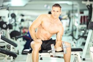homem musculoso sem camisa no banco para levantamento de peso foto