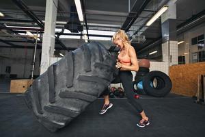 jovem mulher lançando pneu no ginásio foto