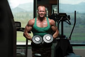 fisiculturista, levantamento de peso com halteres foto