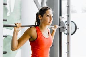 jovem e bela mulher levantando pesos em uma academia