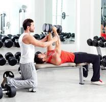 homem de personal trainer academia com musculação foto