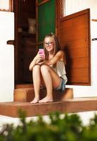 menina caucasiana com celular, casa retrô de madeira