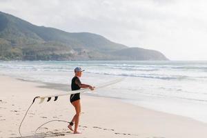 mulher de surf com prancha de surf na praia foto