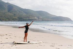 mulher de surf com prancha de surf na praia